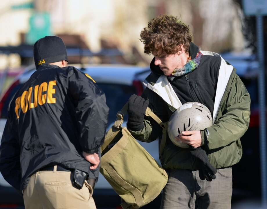 A man who said his name is Niko Sveikauskas is searched by a police official at the scene of a reported suspicious package at the Bank of America branch located at 30 South Water St. in the Byram section of Greenwich, Wednesday, March 26, 2014. Sveikauskas said he was the person who left the package in the bank and had come back to claim it. Photo: Bob Luckey