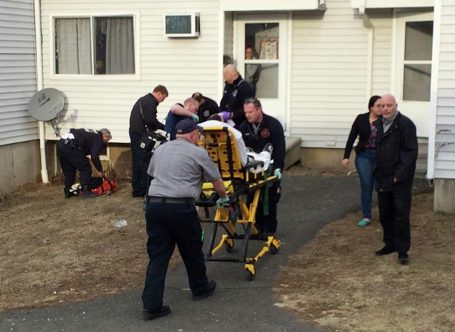 EMTs carry the victim of a shooting on a stretcher at the Beaver Street housing complex in Danbury, Conn. on Thursday, March 27, 2014. Photo: Tyler Sizemore / The News-Times