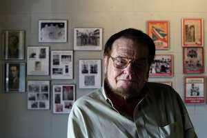 Bruce Hathaway sits in front of images of himself throughout his career hanging on the wall of TEX POP, the South Texas Popular Culture Center, in San Antonio on Tuesday, March 25, 2014.