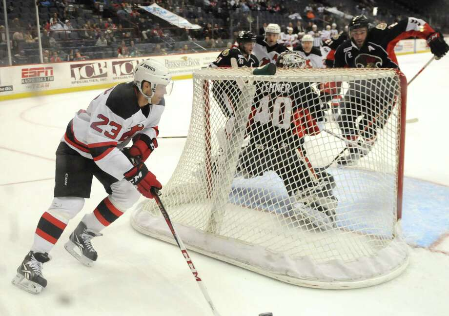 Darcy Zajac of the Albany Devils, left, works behind the Binghamton Senators goal, Sunday evening, Jan. 6, 2013, during the second period at the Times Union Center in Albany, N.Y. Photo: Will Waldron / 00020652B