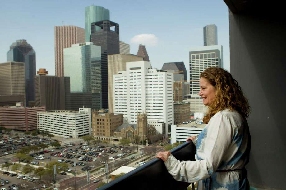 Angela Touchstone stands on her balcony overlooking downtown from her apartment. Photo: Brett Coomer, Staff / © 2014 Houston Chronicle
