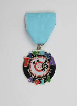 Network for Young Artists' first-ever Fiesta medal features its logo, $10, at the Fiesta Store and the group's office, 1800 Fredericksburg Road, Suite 122, www.nya.us. Photo: Juanito M. Garza, San Antonio Express-News / San Antonio Express-News