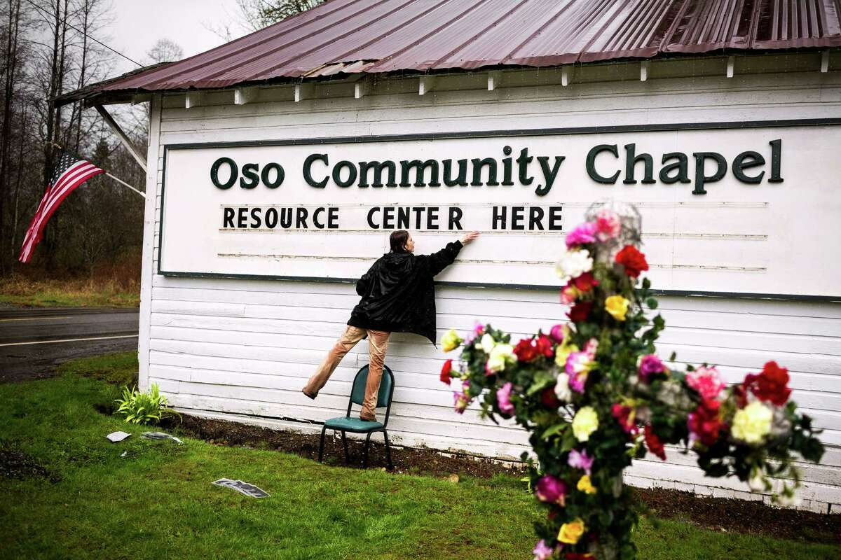 Tina Ray, wife of the pastor of the Oso Community Chapel, helps to spell out a sign to let passersby know of available resources Thursday, March 27, 2014, near Oso within Snohomish County, Wash.