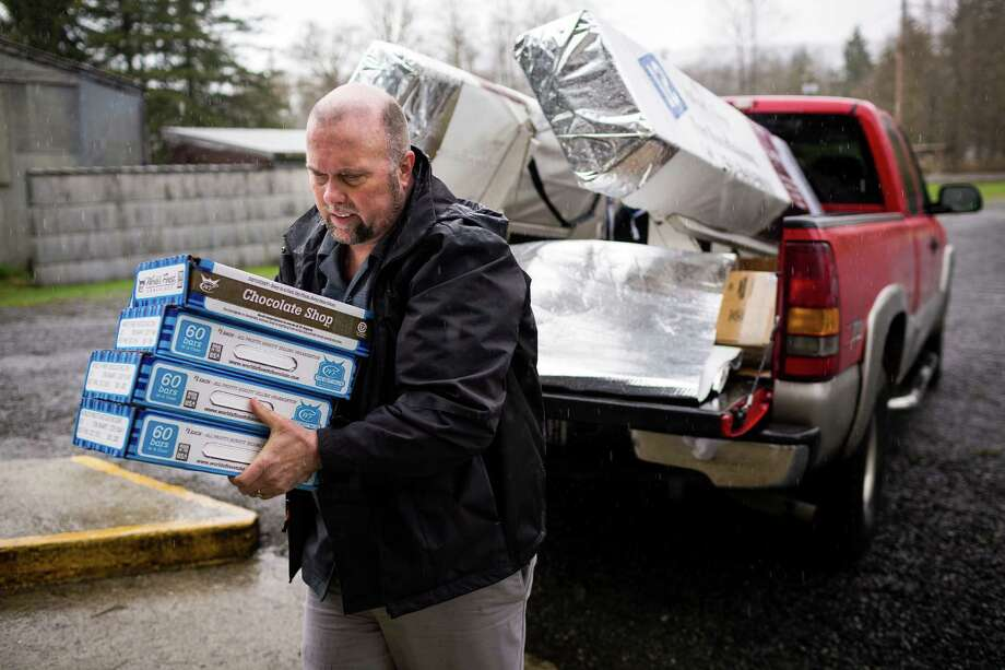 "Gary Ray, pastor of the Oso Community Chapel, helps to load in a truck-full of chocolate bars as a donation for victims to serve as ""comfort food"" Thursday, March 27, 2014, near Oso within Snohomish County, Wash. At least 25 people are known to have died when a colossal mudslide occurred on Saturday, unleashing a wall of earth that destroyed dozens of homes near the rural town of Oso, Wash., 55 miles northeast of Seattle. Photo: JORDAN STEAD, SEATTLEPI.COM / SEATTLEPI.COM"