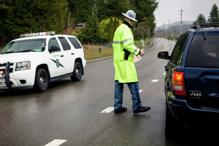 Police keep the public away from the debris area with a roadblock several miles down the road from destruction Thursday, March 27, 2014, near Oso within Snohomish County, Wash. At least 25 people are known to have died when a colossal mudslide occurred on Saturday, unleashing a wall of earth that destroyed dozens of homes near the rural town of Oso, Wash., 55 miles northeast of Seattle. Photo: JORDAN STEAD, SEATTLEPI.COM / SEATTLEPI.COM