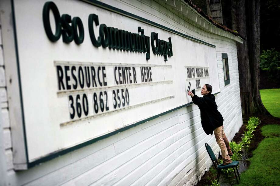 "Tina Ray, wife of the pastor of the Oso Community Chapel, helps to spell out a sign to let passersby know of available resources Thursday, March 27, 2014, near Oso within Snohomish County, Wash. ""The food bank is full, my husband's office is full - he can't even use it,"" Ray said, regarding an outpouring of donations to the church. At least 25 people are known to have died when a colossal mudslide occurred on Saturday, unleashing a wall of earth that destroyed dozens of homes near the rural town of Oso, Wash., 55 miles northeast of Seattle. Photo: JORDAN STEAD, SEATTLEPI.COM / SEATTLEPI.COM"