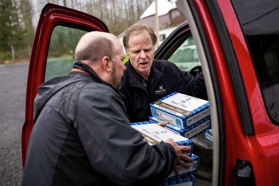 "Gary Ray, left, pastor of the Oso Community Chapel, and Kal Kalamakis, center, of Gig Harbor, Wash., help to load in a truck-full of chocolate bars as a donation for victims to serve as ""comfort food"" Thursday, March 27, 2014, near Oso within Snohomish County, Wash. At least 25 people are known to have died when a colossal mudslide occurred on Saturday, unleashing a wall of earth that destroyed dozens of homes near the rural town of Oso, Wash., 55 miles northeast of Seattle. Photo: JORDAN STEAD, SEATTLEPI.COM / SEATTLEPI.COM"