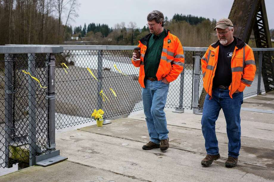 Men walk by yellow ribbons and flowers left for mudslide victims on a bridge above the Stillaguamish River Thursday, March 27, 2014, in Arlington within Snohomish County, Wash. At least 25 people are known to have died when a colossal mudslide occurred on Saturday, unleashing a wall of earth that destroyed dozens of homes near the rural town of Oso, Wash., 55 miles northeast of Seattle. Photo: JORDAN STEAD, SEATTLEPI.COM / SEATTLEPI.COM