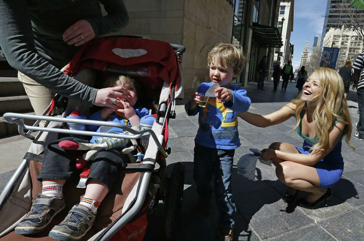 Model Meghan McMahon handed out stickers, literature and juice to promote the Affordable Care Act at a pedestrian mall in Denver last week. Iggy Cole gave a sticker to his brother.