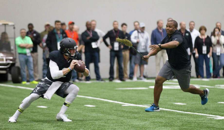 Quarterback guru George Whitfield Jr. provides the pressure on one of Johnny Manziel's throws on Thursday. Photo: Brett Coomer, Houston Chronicle / © 2014 Houston Chronicle