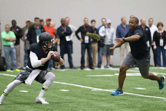 Quarterback guru George Whitfield Jr. provides the pressure on one of Johnny Manziel's throws on Thursday.