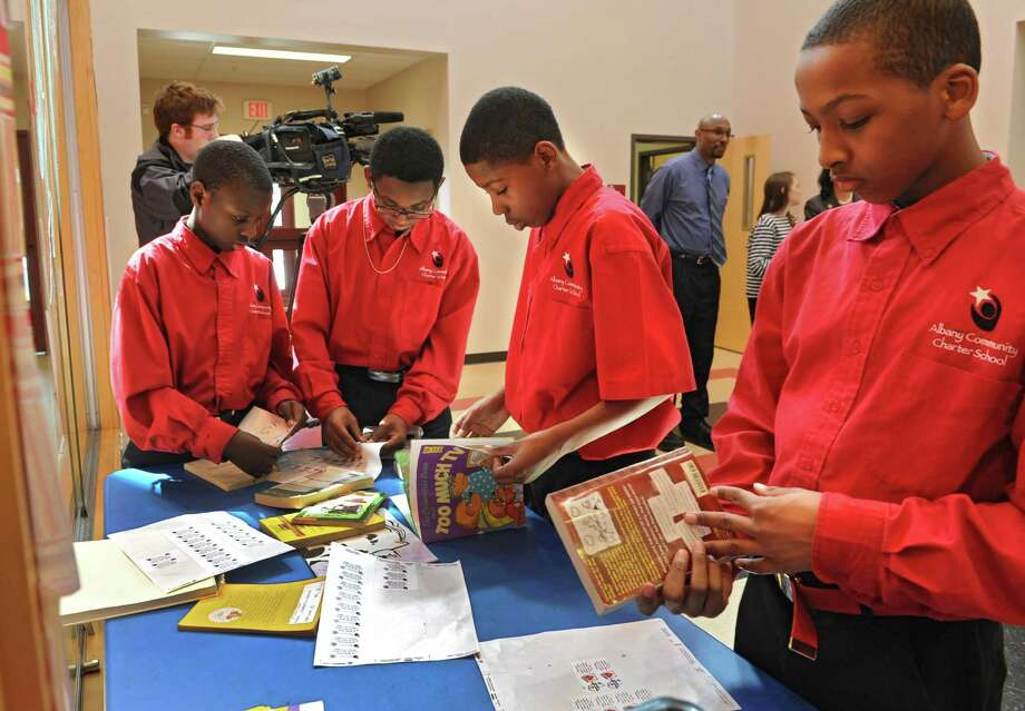 Albany Community Charter School students: Serigne Sow, 12, left, Swayne Ritzie, 13, Rae Quan, 12, and Jordan Simmons, 12, right, put stickers on books as they prepare to ship over 3,000 books to help build a library at the Youth Institute of Science and Technology in Agogo, Ghana Thursday afternorrn, March 27, 2014, in Albany, N.Y. (Lori Van Buren / Times Union) Photo: Lori Van Buren / 00026267A