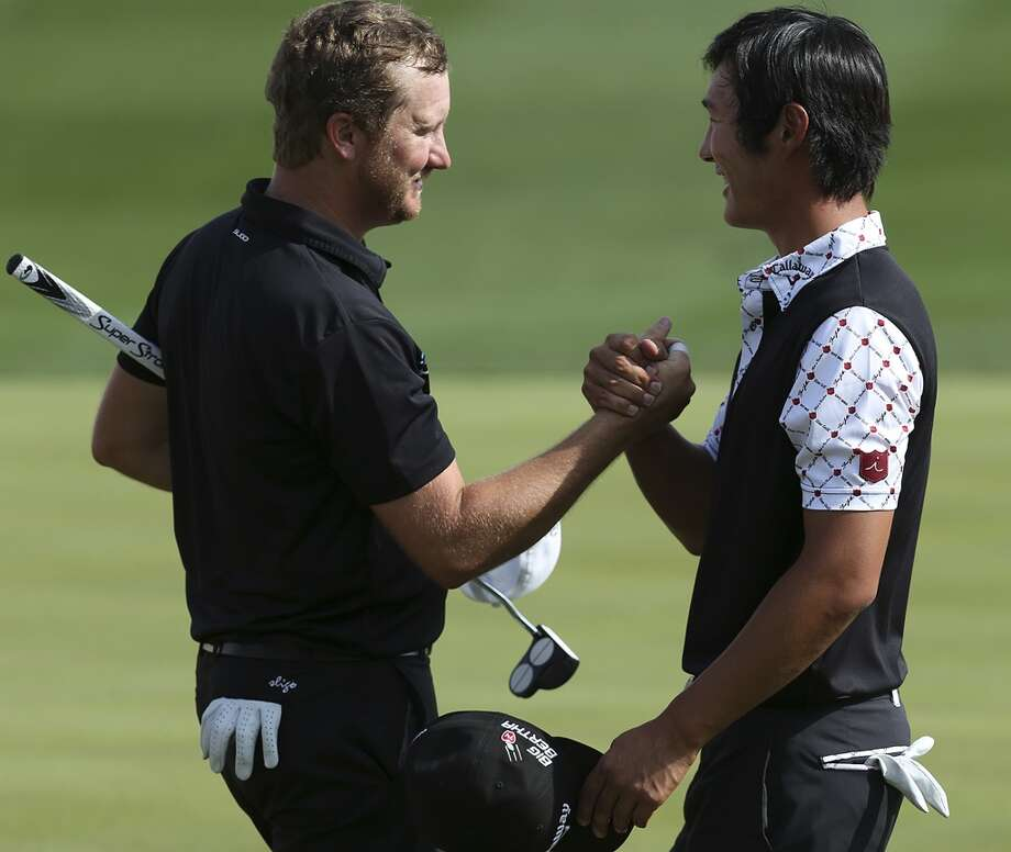 Danny Lee, of Rotorua, New Zealand, right, shakes hands with Brice Garnett, of Gallatin, Missouri, after finishing the first round of the 2014 Valero Texas Open at TPC San Antonio, Thursday, March 27, 2014. Lee birdied the hole and tied for the lead at 4-under with Pat Perez of Scottsdale, Arizona. Garnett ended at two-under and is tied for 5th with twenty other players. Photo: Jerry Lara, San Antonio Express-News