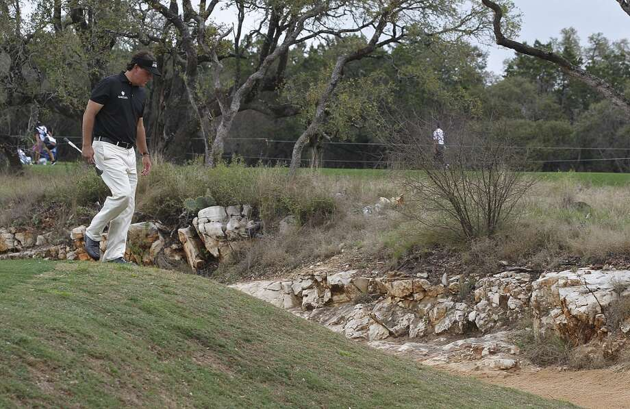 Phil Mickelson, of Rancho Santa Fe, California, checks out the lie of his shot by the number 1 green during the first round of the 2014 Valero Texas Open at TPC San Antonio, Thursday, March 27, 2014. Photo: Jerry Lara, San Antonio Express-News