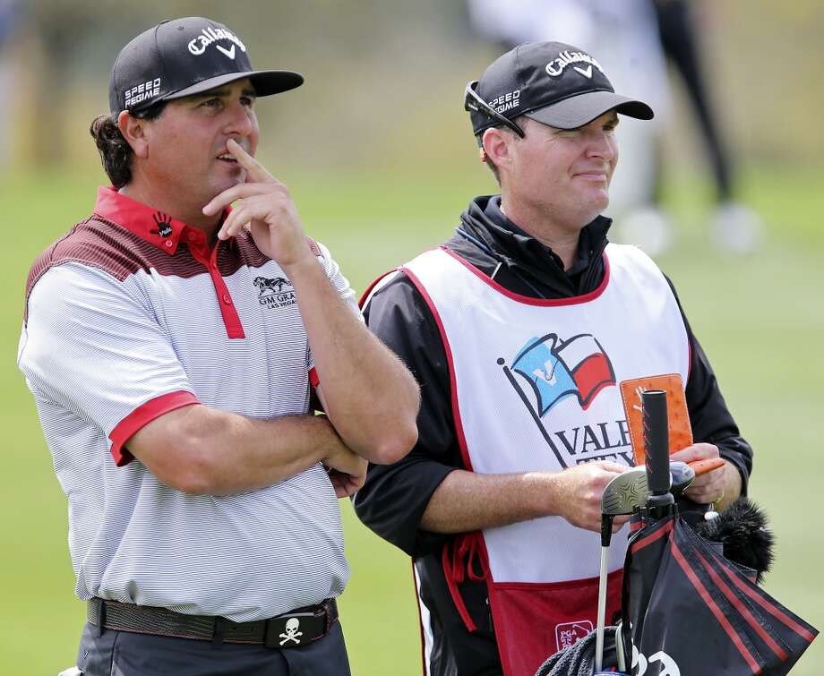 Pat Perez (left) and his caddie Mike Hartford eye the No. 18 fairway during the first round of the 2014 Valero Texas Open Thursday March 27, 2014 at TPC San Antonio. Photo: Edward A. Ornelas, San Antonio Express-News