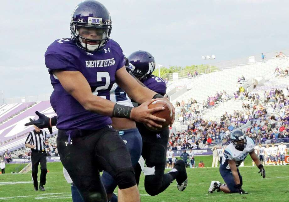 "FILE - In this Sept. 21, 2013 file photo, Northwestern quarterback Kain Colter (2), wears APU for ""All Players United"" on wrist tape as he scores a touchdown during an NCAA college football game against Maine in Evanston, Ill. The decision to allow Northwestern football players to unionize raises an array of questions for college sports. Among them, state schools vs. public schools, powerhouse programs vs. smaller colleges.  (AP Photo/Nam Y. Huh, File) ORG XMIT: CER101 Photo: Nam Y. Huh / AP"