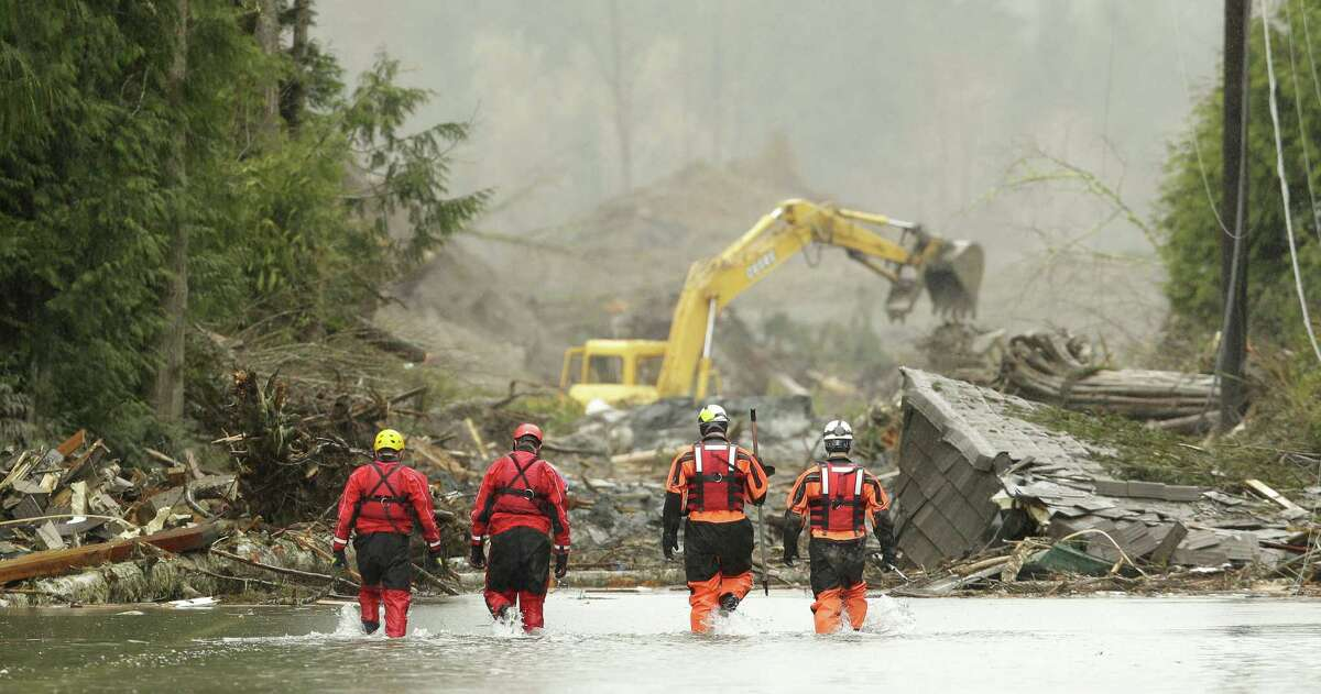 Search and rescue workers wade through water covering Washington Highway 530 on the eastern edge of the massive mudslide that struck Saturday near Darrington, Wash.