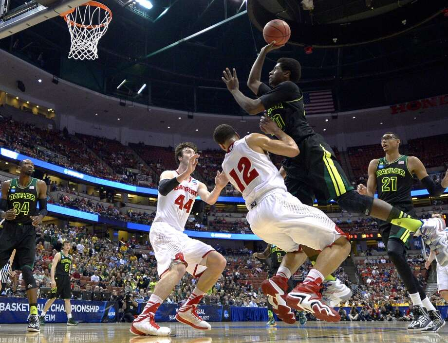 Baylor forward Royce O'Neale, right, shoots over Wisconsin guard Traevon Jackson (12) as Wisconsin forward Frank Kaminsky (44) defends during the first half of an NCAA men's college basketball tournament regional semifinal, Thursday, March 27, 2014, in Anaheim, Calif. Photo: Mark J. Terrill, Associated Press