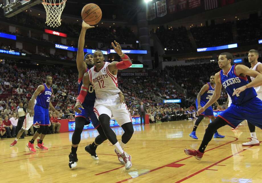Rockets center Dwight Howard loses the ball while defended by Philadelphia's Brandon Davies. Photo: Johnny Hanson, Houston Chronicle