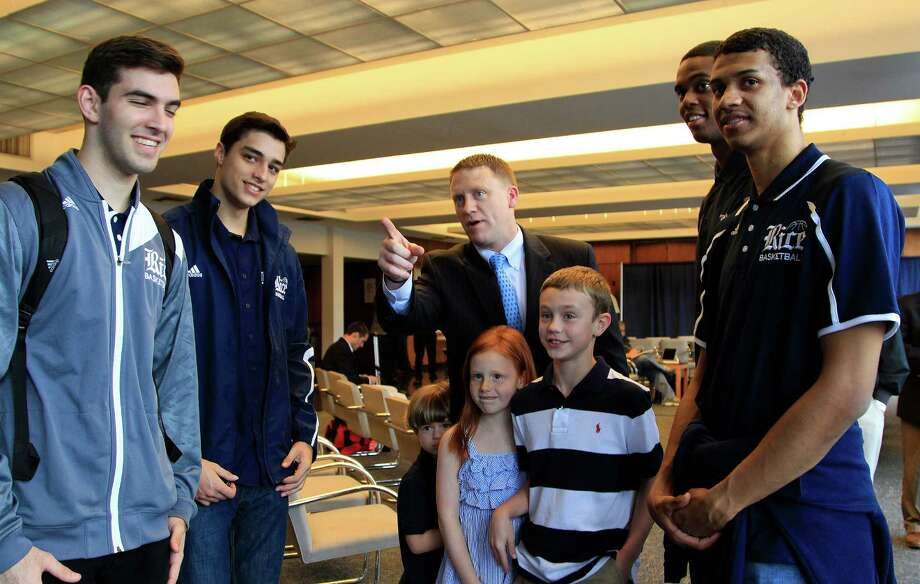 """It was """"Meet the Owls Day"""" as Mike Rhoades, center, introduces son Logan, 10, and daughter Porter, 8, to several Rice basketball players before Thursday's news conference introducing Rhoades as the school's new coach. Photo: Karen Warren, Staff / © 2014 Houston Chronicle"""