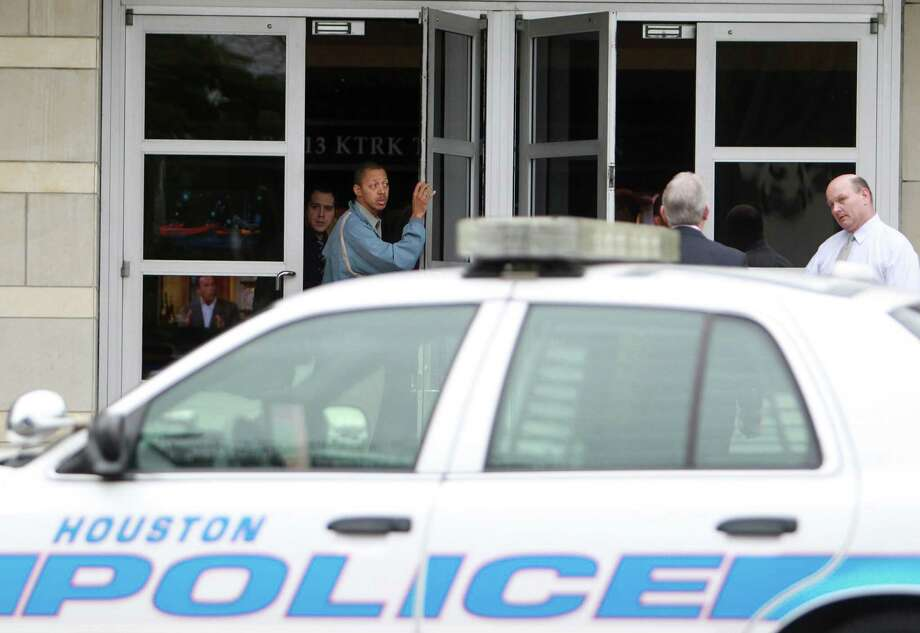 Channel 13 staff stay inside as Houston Police officers investigate why a woman opened fire on the studio Thursday. Photo: Mayra Beltran, Staff / © 2014 Houston Chronicle