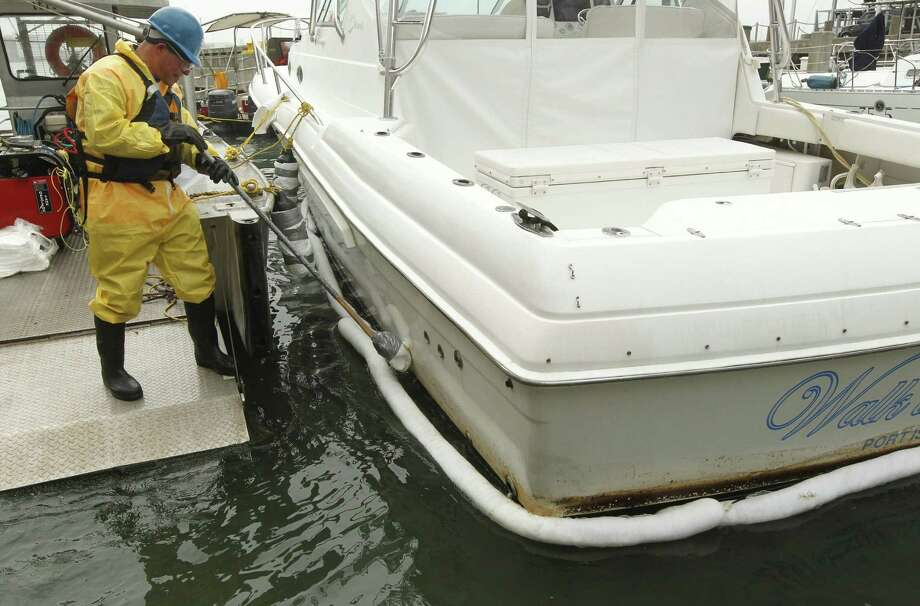 Heberto Bruno wipes heavy fuel oil from the hull of a boat docked in Galveston. Saturday's oil spill has killed at least 37 oiled birds in and around Galveston Bay, officials say. Photo: Jennifer Reynolds / Galveston Daily News / The Galveston County Daily News