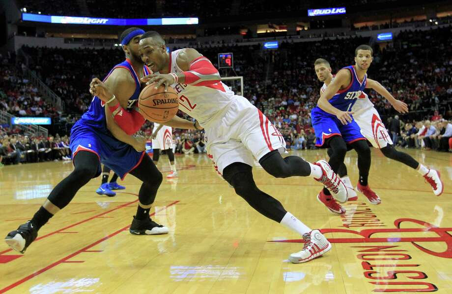Dwight Howard, driving on the Sixers' Brandon Davies, was limited to 26 minutes Thursday night as his left ankle began to bother him. Photo: Johnny Hanson, Staff / © 2014  Houston Chronicle