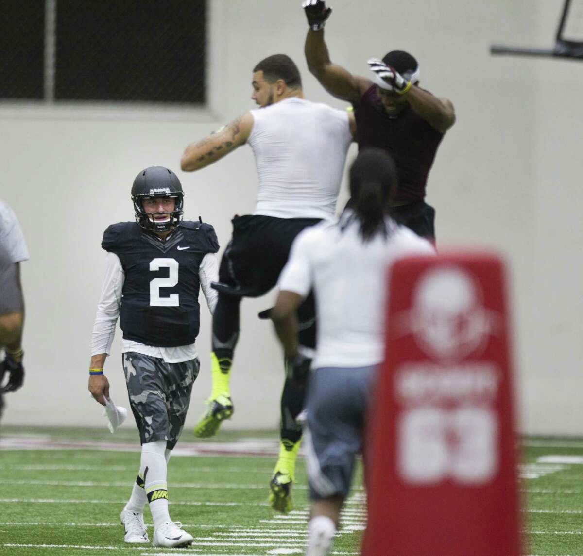 Ex-A&M QB Johnny Manziel (2) walks off the field as WR Mike Evans (center) and another player celebrate. New Texans coach Bill O'Brien was among those attending the Aggies' pro day.