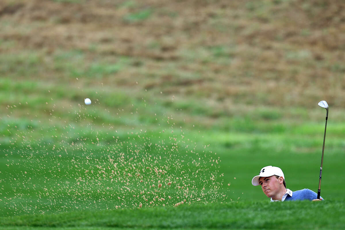 Jordan Spieth shoots out of a bunker by the 10th green during the first round of the 2014 Texas Open at TPC San Antonio, Thursday, March 27, 2014.