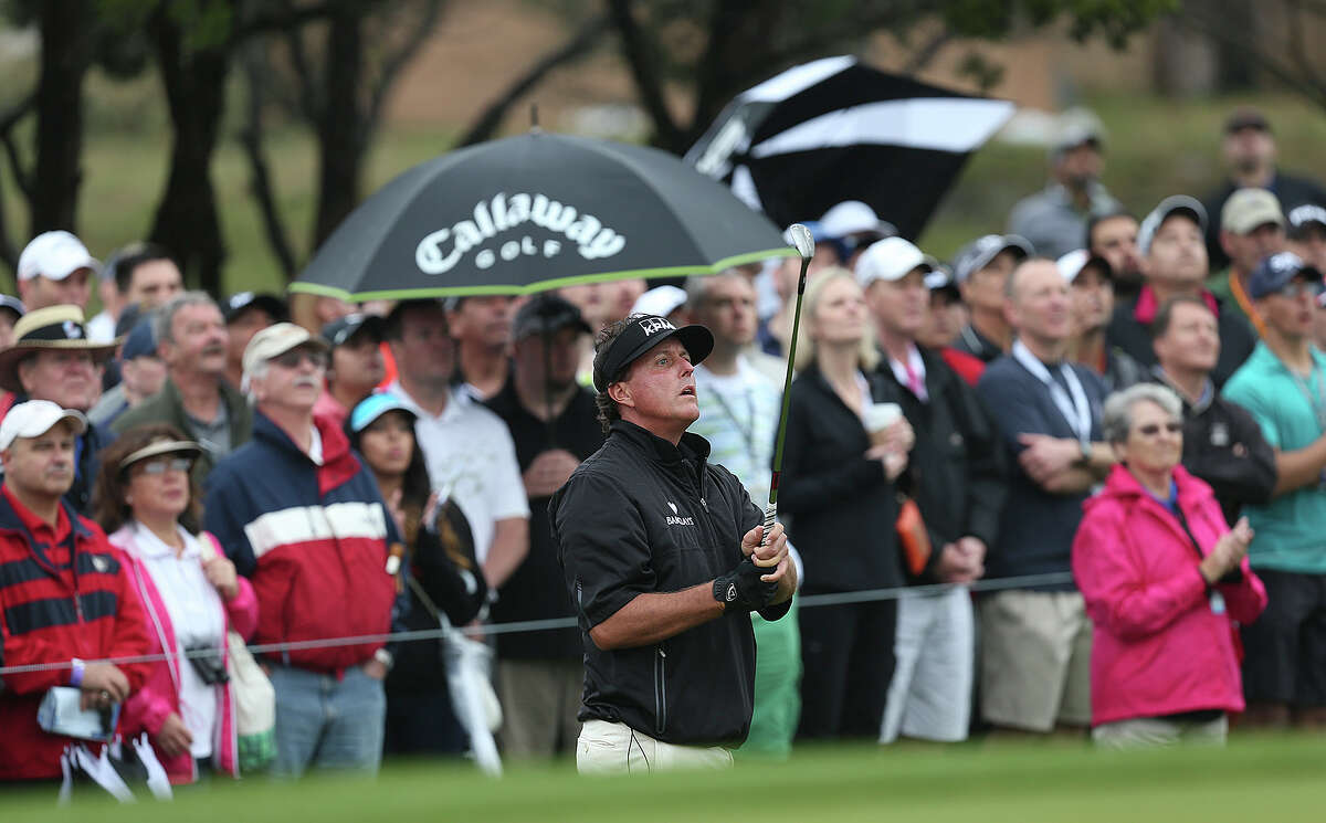 Phil Mickelson looks at his shot on to the 10th green during the first round of the 2014 Texas Open at TPC San Antonio, Thursday, March 27, 2014.