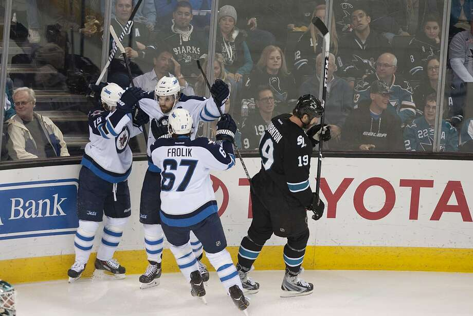 Winnipeg's Bryan Little (left) and Michael Frolik celebrate with Andrew Ladd after his first-period goal. Photo: Ed Szczepanski, Reuters