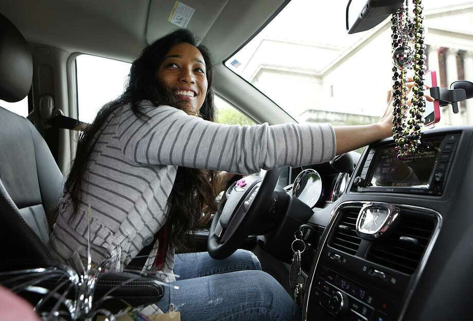On Yong Theus a driver with LYFT, sets her GPS on her phone for directions during a fare. LYFT drivers use their own cars to drive passengers as a taxi would. Theus has decorated her car with a disco theme which was her daughter's idea.  Thursday, March 27, 2014. Photo: San Antonio Express-News / © 2012 San Antonio Express-News