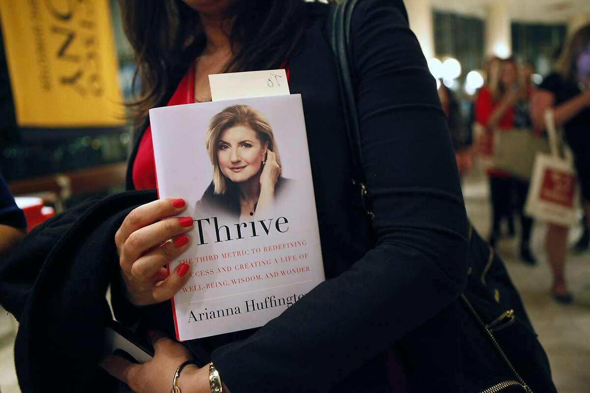 A woman holds Arianna Huffington's book while she waits in line to have it signed, following Arianna's interviewed with Sheryl Sandberg, held by the Commonwealth Club at Davies Symphony Hall in San Francisco, CA, Thursday March 27, 2014.
