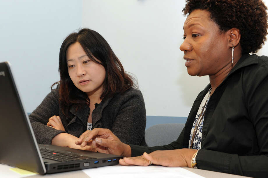 Loretta Ebron, right, a Certified Application and Outreach Councilor, helps client Young Lee, of Bridgeport, as she signs up for state health care at Optimus Health Care, in Bridgeport, Conn. March 28, 2014. Photo: Ned Gerard / Connecticut Post