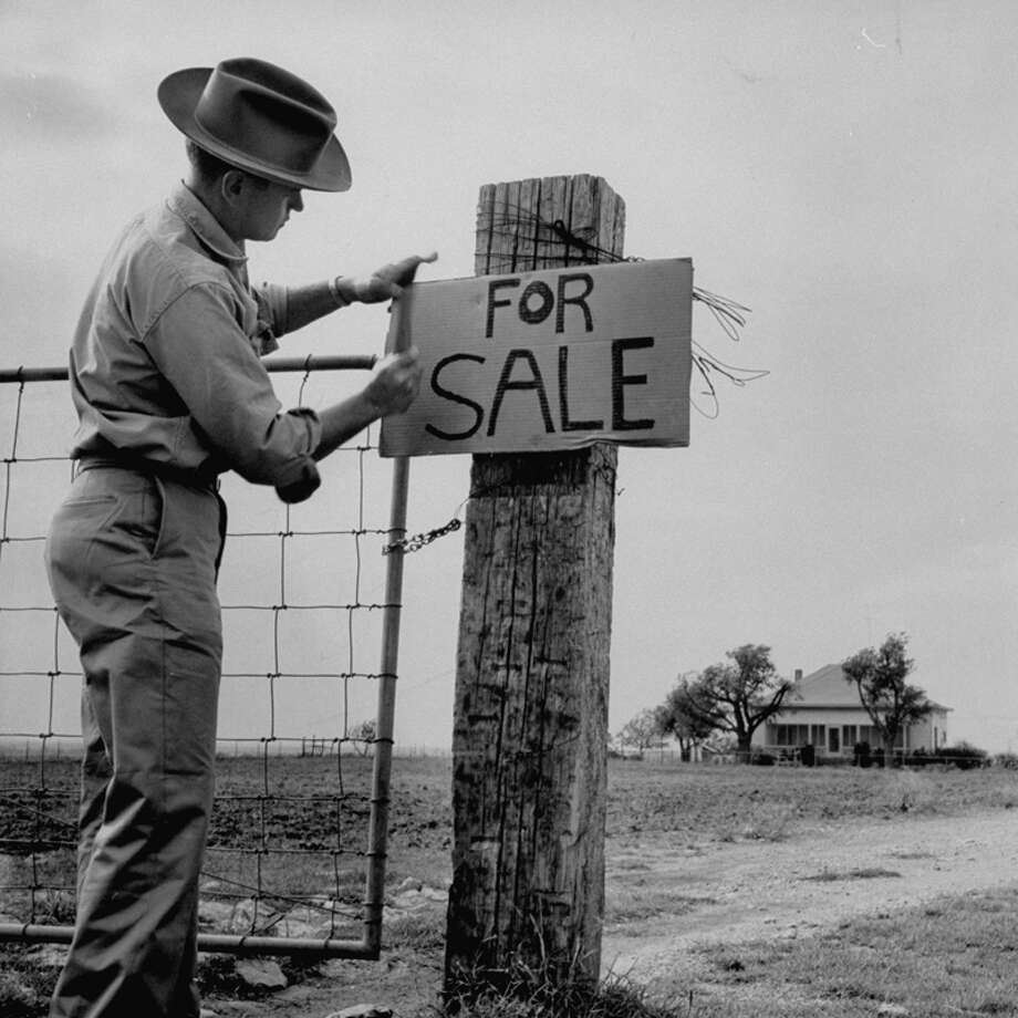 Alex Dickie Jr., Texas cattle man on ranch ruined by drought, seeking a drastic method to pay off his bills, puts a For Sale sign up.  (Photo by A. Y. Owen//Time Life Pictures/Getty Images) Photo: A. Y. Owen, Time & Life Pictures/Getty Image / Time Life Pictures