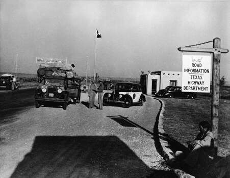 Displaced farm workers from Oklahoma, referred to as Okies, stop at Road Information on the Texas state border as they flee the Dust Bowl, Texas, 1930s. A man, probably Native American, sits against the sign for Road Information. (Photo by American Stock/Getty Images) Photo: American Stock Archive, Getty Images
