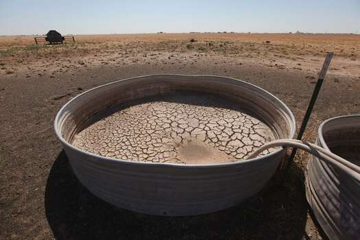 Cracked mud lines the bottom of a water tank in a pasture July 28, 2011 near Tulia, Texas. A dead cow and calf lay in the field nearby. A severe drought in the region has caused shortages of grass, hay and water, forcing ranchers to thin their herds or risk losing their cattle to the drought. The past nine months have been the driest in Texas since record keeping began in 1895, with 75% of the state classified as exceptional drought, the worst level.  (Photo by Scott Olson/Getty Images) Photo: Scott Olson, Getty Images