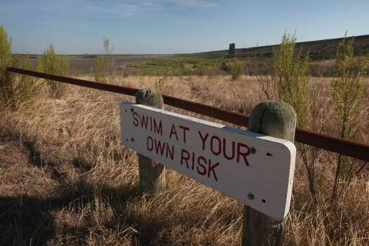 A warning to swimmers is posted along the shore of the dried O.C. Fisher Lake on July 25, 2011 in San Angelo, Texas. The 5,440 acre lake which was established to provide flood control and serve as a secondary drinking water source for San Angelo and the surrounding communities is now dry following an extended drought in the region. The lake which has a maximum depth of 58 feet is also used for boating, fishing and swimming. The San Angelo area has seen only 2.5 inches of rain this year. The past nine months have been the driest in Texas since record keeping began in 1895, with 75% of the state classified as exceptional drought, the worst level.  (Photo by Scott Olson/Getty Images) Photo: Scott Olson, Getty Images