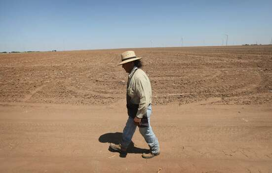 "HERMLEIGH, TX - JULY 27: Juan Rico walks by a barren cotton field July 27, 2011 near Hermleigh, Texas. A severe drought has caused the majority of dry-land (non-irrigated fields) cotton crops to fail in the region. The past nine months have been the driest in Texas since record keeping began in 1895, with 75% of the state classified as ""exceptional drought"", the highest classification.  (Photo by Scott Olson/Getty Images) Photo: Scott Olson, Getty Images"