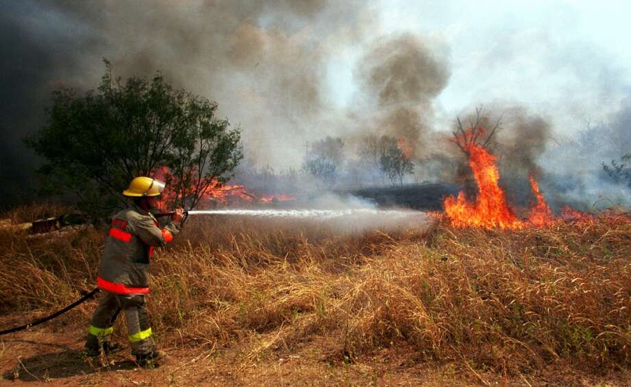 A firefighter battles a fast moving grass fire, September 7, 2000 in Ranger, Texas. Forest fires and grass fires continue to burn across Texas as the state enters its 68th consecutive day without rain. (Photo by Joe Raedle/Newsmakers) Photo: Joe Raedle, Getty Images