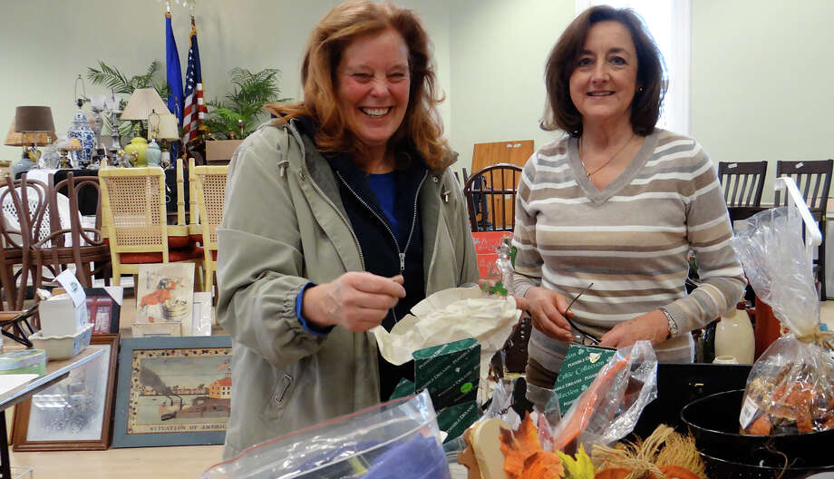 Volunteer Conchita Cassell, right, assists shopper Jane Seymour, of Norwalk, with holiday items at the Westport Woman's Club Curio Cottage Thrift Shop Tag Sale on Friday morning. Photo: Mike Lauterborn / Westport News