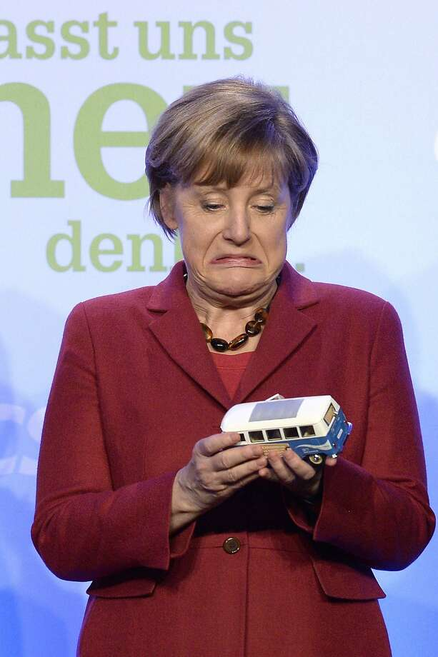 I was hoping for a Mercedes! German Chancellor Angela Merkel examines a model of an old  