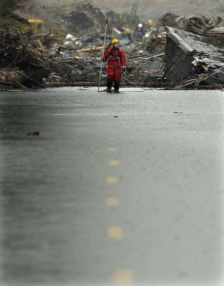 Searching for the victims: A search-and-rescue worker carrying a probe wades through water covering Washington Highway 