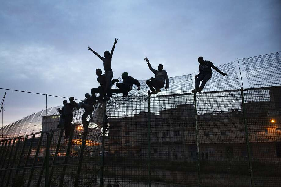 Sub-Saharan migrants climb over a metallic fence that divides Morocco and the Spanish enclave of Melilla on Friday March 28, 2014. Officials said several hundred African migrants tried to cross barbed-wire border fences to enter the Spanish enclave of Melilla from Morocco but most were turned back by security forces from both sides. An Interior Ministry spokesman in Melilla said the migrants attempted to scale the fences several times early Friday and a handful managed to get across. Thousands of migrants seeking a better life in Europe are living illegally in Morocco, hoping they can enter Melilla and Spain's other north African coastal enclave, Ceuta. (AP Photo/Santi Palacios) Photo: Santi Palacios, Associated Press