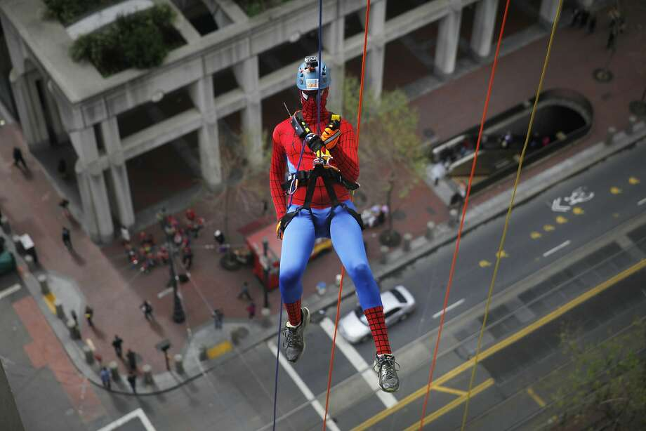Sebastian Joll of San Francisco hovers above Market Street as he rappels 23 stories down the side of the Hyatt Regency at Embarcadero Center. Photo: Lea Suzuki, The Chronicle