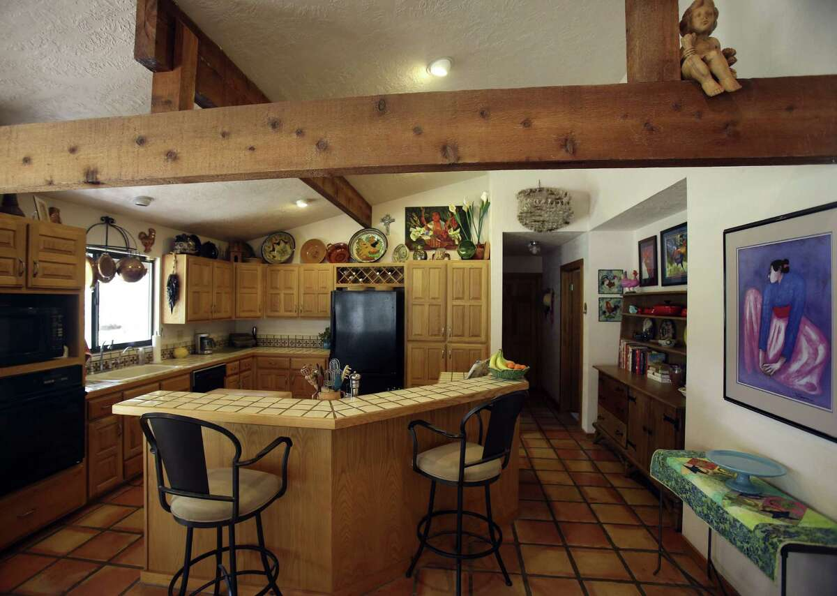 The beamed ceiling and tile counters blend New Mexico style with functionality in the kitchen.