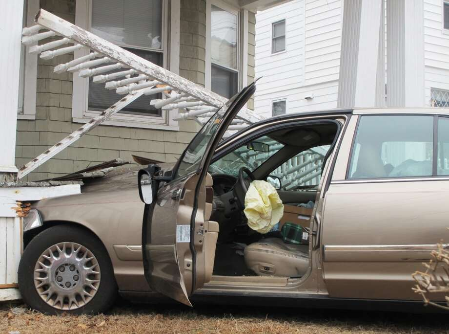 A car struck a house at 156 Savoy Street in Bridgeport, Conn. on March 28, 2014. The collision damaged the house's porch but there were no reported injuries. Photo: Wes Duplantier, Connecticut Post