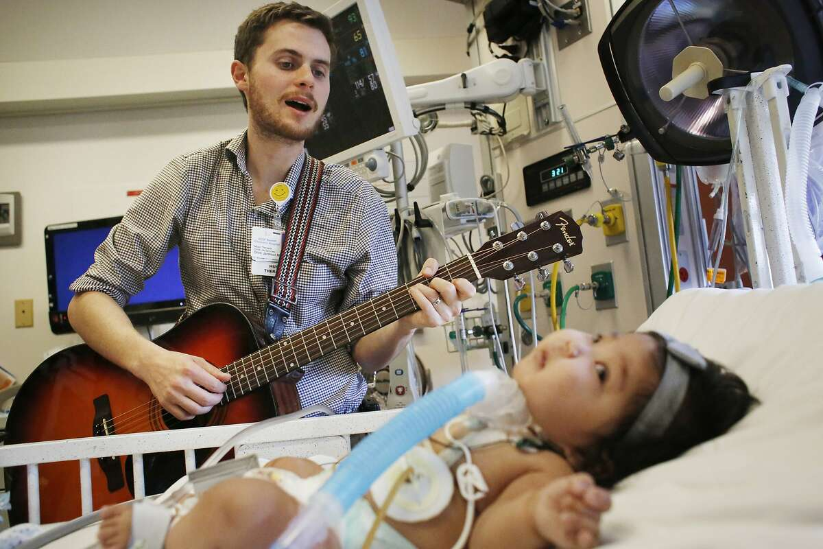 Oliver Jacobson, music therapist at UCSF Benioff Children's Hospital, sings to Maia Mead.