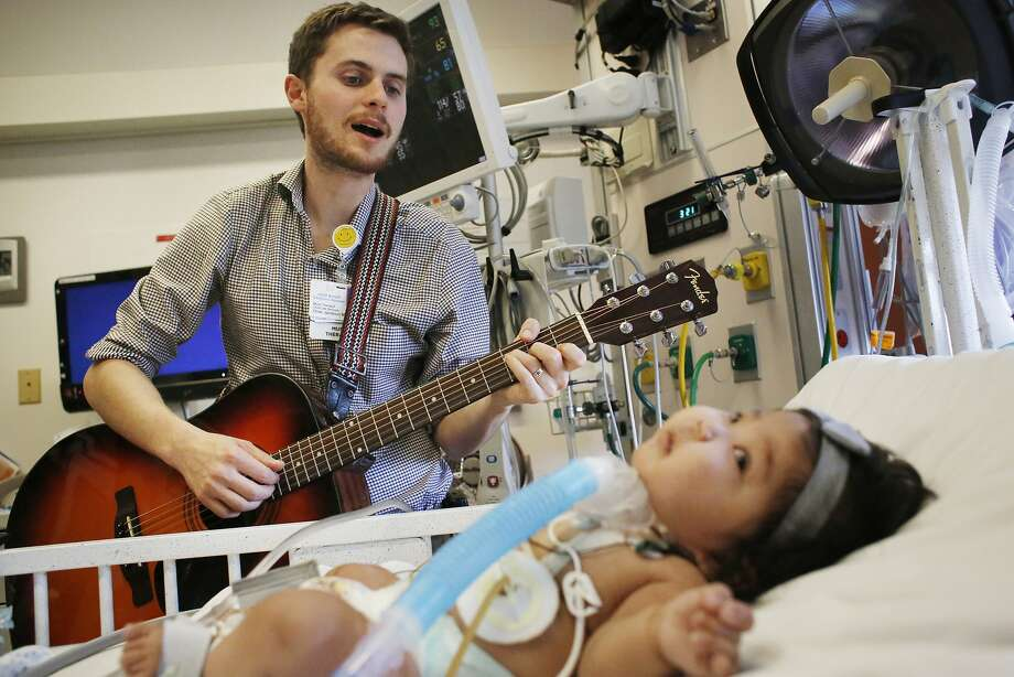 Oliver Jacobson, music therapist at UCSF Benioff Children's Hospital, sings to Maia Mead. Photo: Mike Kepka, The Chronicle
