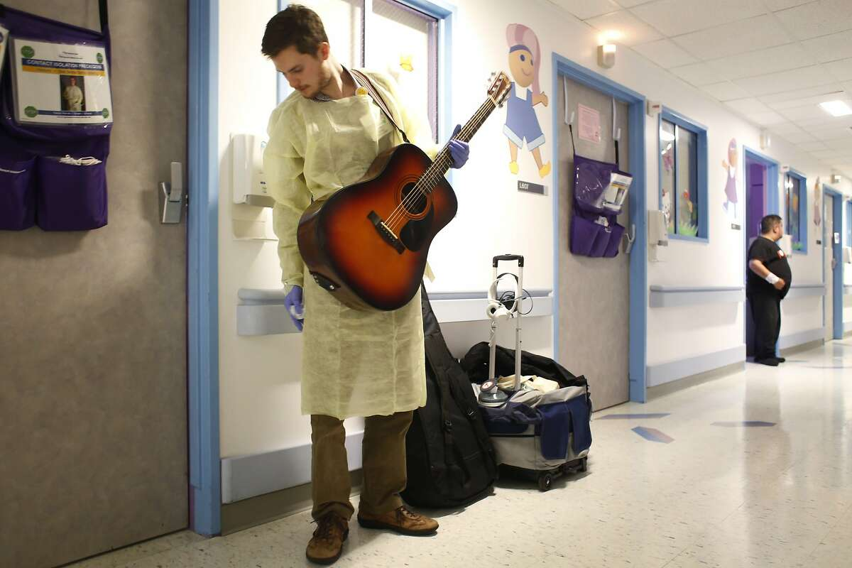 Adjusting his gloves and paper gown, Oliver Jacobson prepares to sing to an immune-compromised patient at UCSF Benioff Children's Hospital.